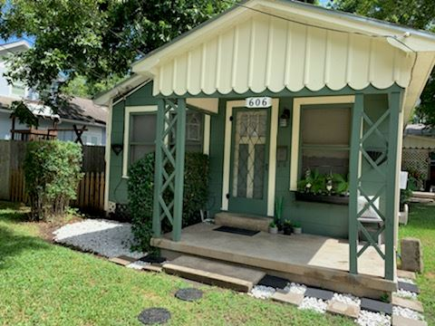 Room and Boards, front porch of dark green painted cottage