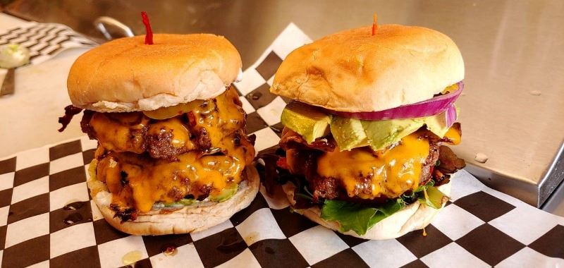 Two delicious burgers loaded with melting cheese, meat and vegtables.