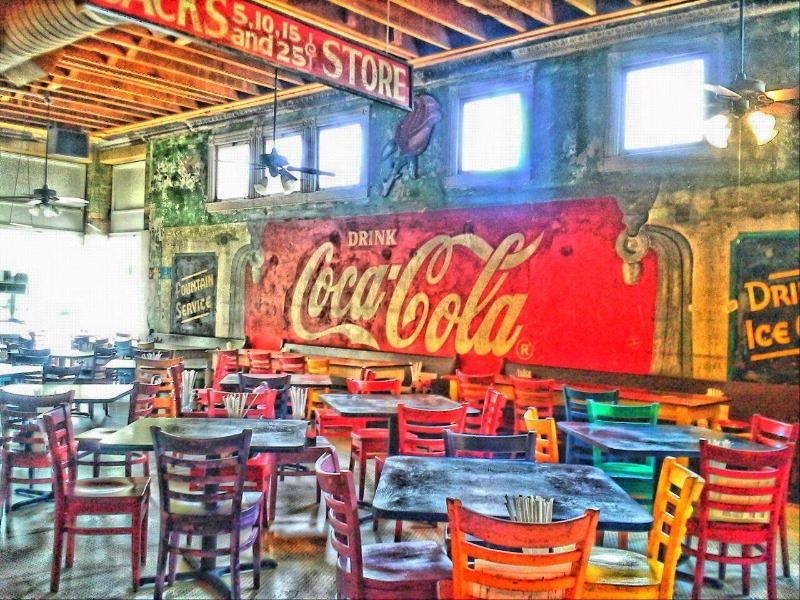 Inside the dining room of Rosebuds Cafe with colorful chairs and tables and a ghost Coca-cola sign.